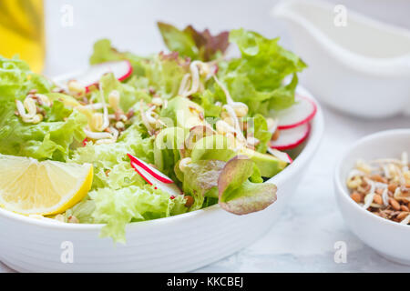 Green vegetable salad with sprouts, beetroot and hummus. Healthy detox vegan food concept. - Stock Photo