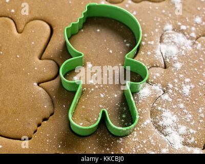 view of green cookie cutter on cookie dough - Stock Photo
