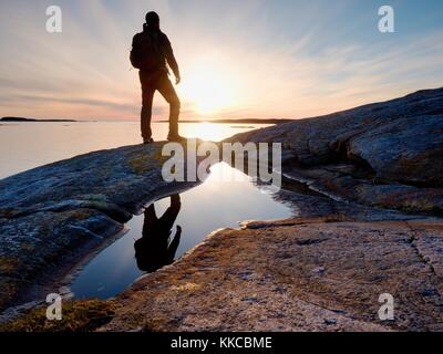 Tall backpacker watch clear sunny spring daybreak over sea. Hiker with backpack stand on rocky shore and his figure - Stock Photo
