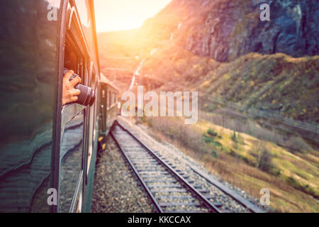 Tourist taking pictures with a dslr camera during trip on the famous scenic train line in Norway going from Myrdal - Stock Photo
