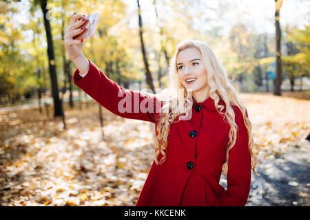 Teenage girl in autumn in park taking a selfie on smart phone. Beautiful happy young woman taking a photo of herself - Stock Photo