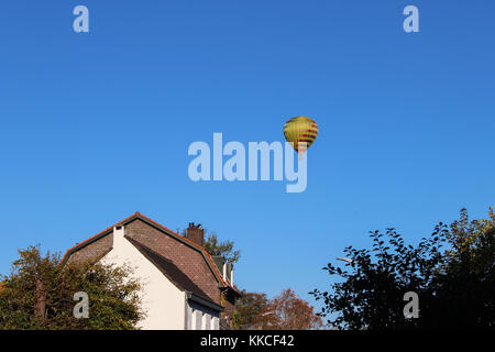 View of a multicolored hot air balloon flying over the Dutch countryside. - Stock Photo