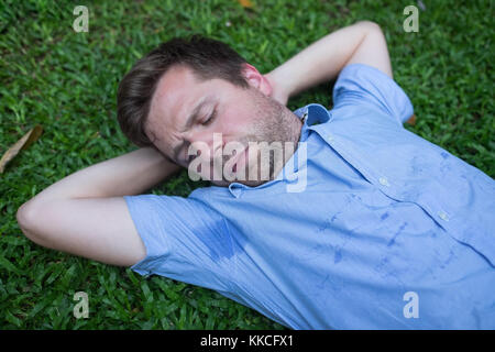 Caucasian, young man is resting on green grass and looking on his wet shirt. - Stock Photo