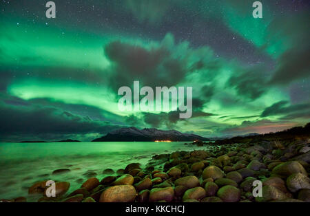 Aurora Borealis or northern lights over winter landscape in fjord of Kaldfjord, Tromvik, Tromso, Troms, Norway, - Stock Photo