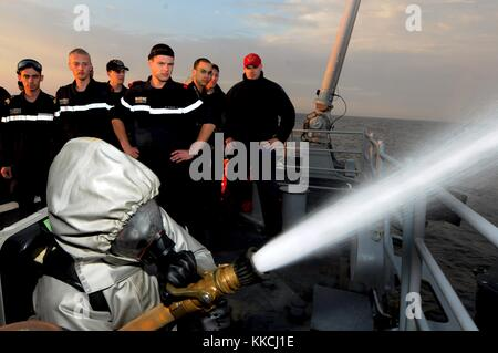 Hull Technician 1st Class Robert Kinast, right, observes a French sailor demonstrating fire fighting techniques - Stock Photo