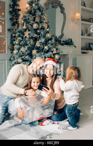 Cheerful family making comic xmas selfie and showing tongues - Stock Photo