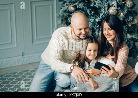 miling young family in Christmas atmosphere making photo with smartphone - Stock Photo