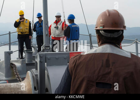 HOSOSHIMA, Japan (Nov. 25, 2017) Sailors lower the anchor during an anchoring evolution aboard the Avenger-class - Stock Photo