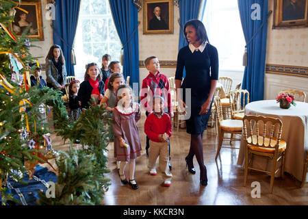 First Lady Michelle Obama walks with children past the official White House Christmas Tree in the Blue Room, Nov. - Stock Photo