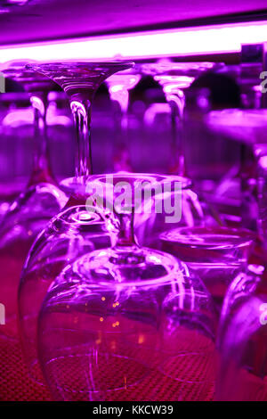 Abstract photo of glasses from a bar with a purple light. - Stock Photo