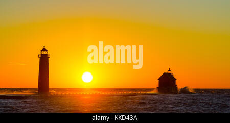 The sun sets behind the Grand Haven, Michigan, lighthouse and pier on Lake Michigan. - Stock Photo