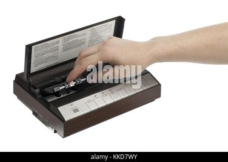 view of a person putting cassette inside player - Stock Photo