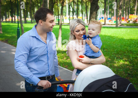 nice family walking along alleys in park - Stock Photo