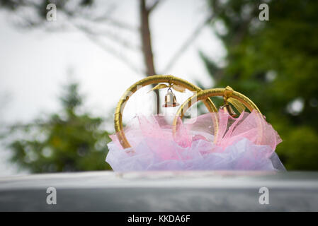Wedding rings and decoration on the roof of the car on outdoor blurred green background. - Stock Photo