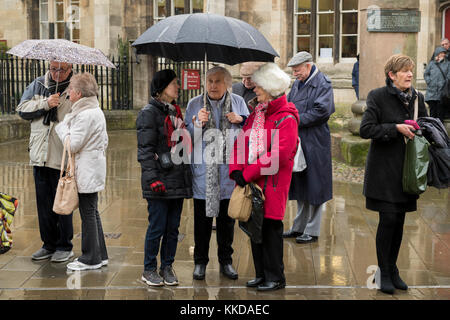 Men & women standing in rain, sheltering under umbrellas, waiting patiently for parade to start - near York Minster, - Stock Photo
