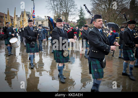 Pipe band marching & playing in rain during parade near York Minster on 50th anniversary of British withdrawal from - Stock Photo