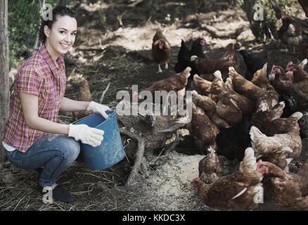 cheerful woman farmer standing with bucket and feeding chickens on farm yard - Stock Photo