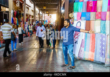 Dubai, UAE, February 5, 2016: Bustling shopping street of Dubai Textile Souk in Bur Dubai - Stock Photo