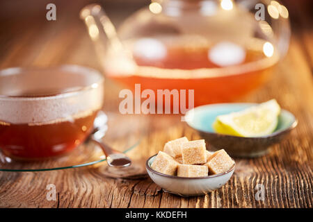 Hot russian tea in cup and teapot and brown sugar cubes and lemon on brown wooden table - Stock Photo