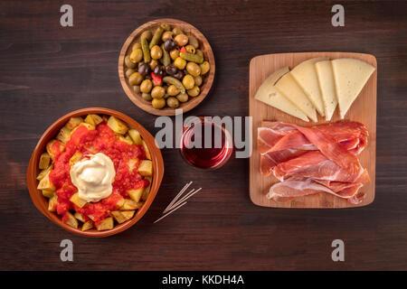 Tapas and wine. Patatas bravas, olives, jamon, cheese - Stock Photo