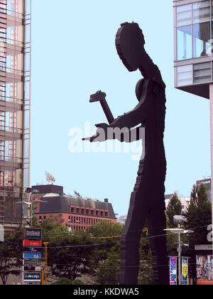 Seoul Hammering Man its the largest of the Hammering Man standing 72 feet high.  Hammering Man's arm 'hammers' silently - Stock Photo