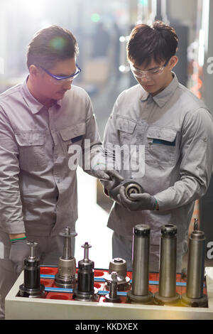 Confident Chinese engineers working in the factory - Stock Photo