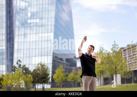 A man making hand gestures while standing in front of modern glass building. - Stock Photo