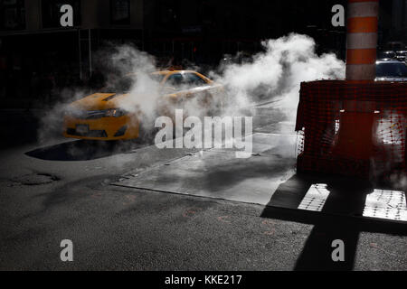 Taxi driving through steam leak in New York City - Stock Photo
