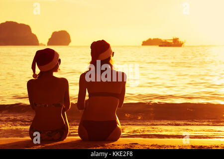Two ladies in christmas caps at sunset beach - Stock Photo