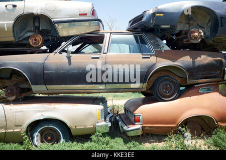 Stack of old rusting cars in a breakers yard or scrap yard neatly piled on top of one another - Stock Photo