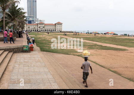 A vendor carries his goods on his head at Galle Face Green in Colombo, Sri Lanka. - Stock Photo