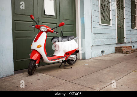 Red and white scooter parked outside a green door on the side walk in a transportation concept - Stock Photo