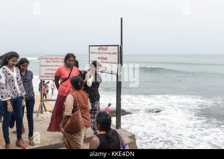 Women look at the sea at Galle Face Green in Colombo, Sri Lanka. - Stock Photo