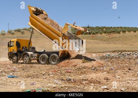 Truck unloading soil in landfill site - Stock Photo