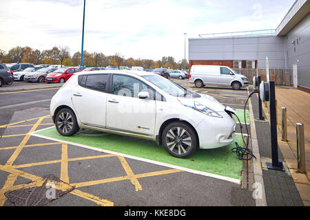 Burtonwood shopping centre in Warrington, an electric Nissan Leaf car parked in a dedicated parking bay for recharging - Stock Photo
