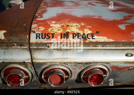 Fun message on an old rusty car - Rust In Peace - on the rear of a vintage Chevrolet with advanced corrosion - Stock Photo