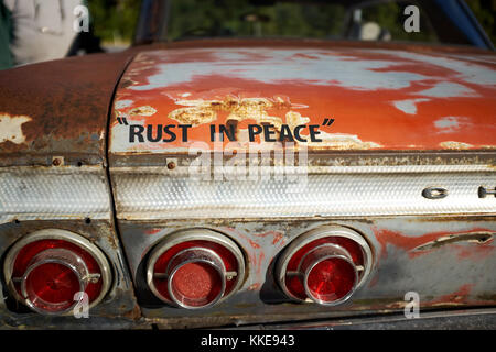 Old rusting vintage Chevrolet with fun text stencilled onto the boot lid - Rust in Peace - in a close up view - Stock Photo