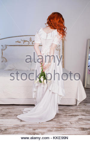 Portrait of a woman with long red curly hair in a white vintage wedding dress with white pearl earrings on her ears. - Stock Photo