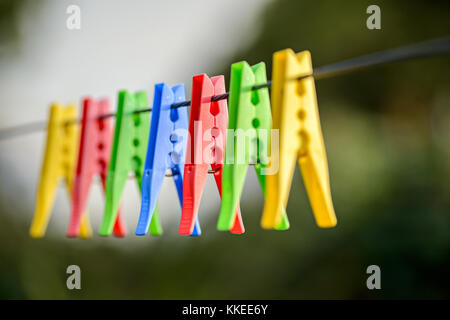 Colorful pegs hanging on clothesline - Stock Photo