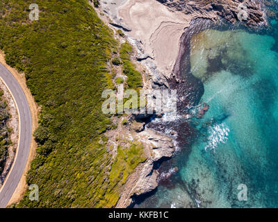 Aerial view of the coast of Corsica, winding roads and coves with crystalline sea. Cap Corse Peninsula, Corsica. - Stock Photo