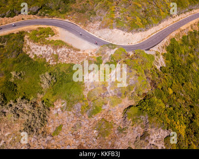 Aerial view of the coast of Corsica, winding roads. Cyclists running on a road. Peninsula of Cap Corse, Corsica. - Stock Photo