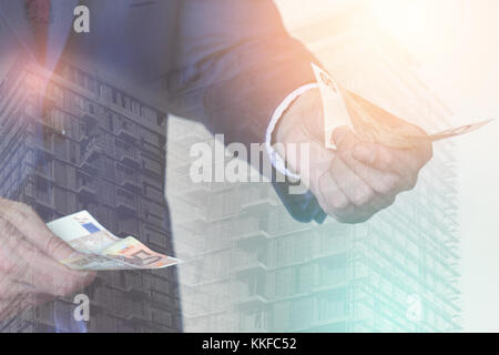 Double exposure of businessman with money in his hands and construction sight behind him; corruption concept - Stock Photo