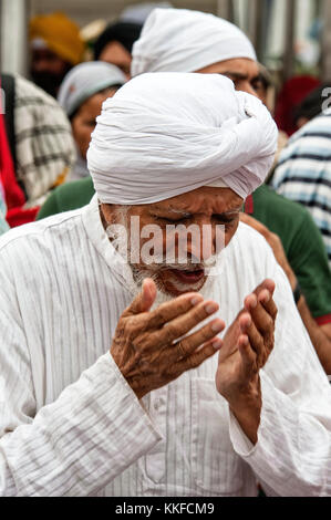Sikh man at Gurudwara temple - New Delhi, India Old Indian Sikh man in traditional dress visiting Gurudwara temple, - Stock Photo