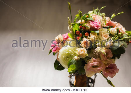 Wedding bouquet of white, red and pink flowers in a vintage vase stands on a light background. White and pink roses. - Stock Photo