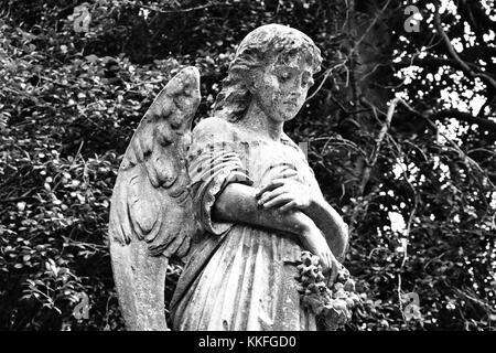 A pensive angel blows her head in sorrow over a grave in historic Hollywood Cemetery in Richmond, Virginia. - Stock Photo