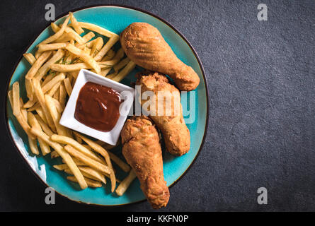 French fries and fried chicken legs on dark background with blank space - Stock Photo