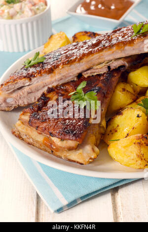 Fresh baked golden potatoes and beef ribs in bbq sauce on wooden background,selective focus - Stock Photo