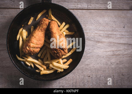 Fried chicken legs and french fries in the pan,blank space on the right side - Stock Photo