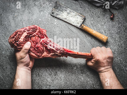 Raw tomahawk beef steak in male hands with meat cleaver on dark rustic background. Butcher hands holding tomahawk - Stock Photo