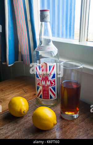 Empty bottle of Pimms with glass of Pimms drink and two lemons on wooden table by window - Stock Photo